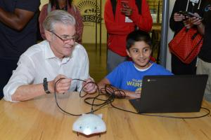 Tom Torlakson enjoys a tech activity with a young student